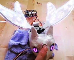 Un petit robot compagnon dragon violet avec plume d'Adafruit